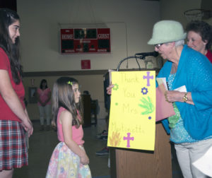 Norma Martinetti receives a gift of appreciation from a student.