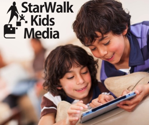 Two boys use a tablet to read a StarWalk Kids book.