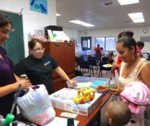 Godoy (center left) helps young parents with baby items.