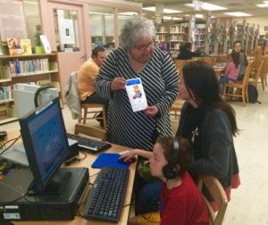"""County Librarian Nora Conte' explains their newest campaign """"One Thousand books before 1st Grade"""" campaign to Elidra Lozana and Jose' Perez."""