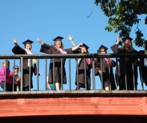 Graduates cross the campus bridge during the procession as an annual tradition