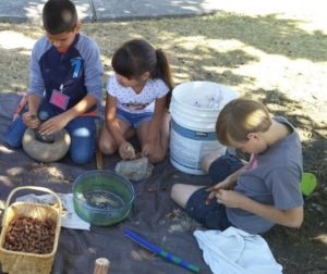 Discovery Camp participants grinding acorns. Photo courtesy of Kanyon Sayers-Roods.