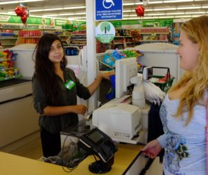 Renate Ramirez selects two food items for Jessica Bueno to ring up as donations to Community Food Bank.