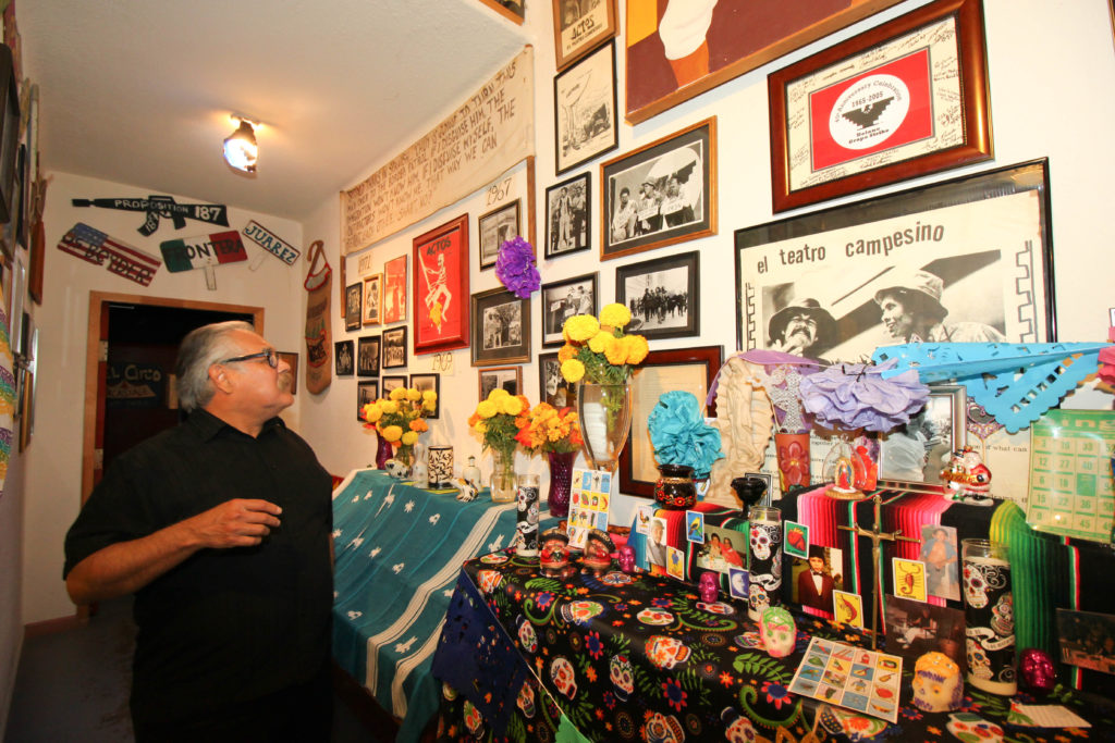 Luis Valdez looking over the leaflet that announced the formation of El Teatro Campesino. Photo courtesy of Donna Silva (DLynn Photography).