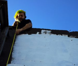 Artist Joel Esqueda measures the wall