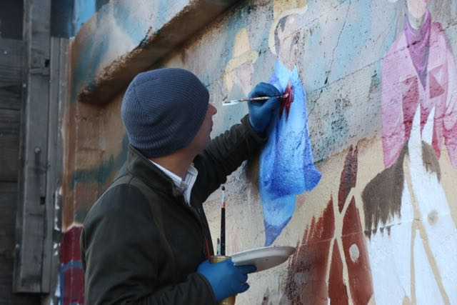Phillip Orabuena, the main artist on the mural paints at all hours.