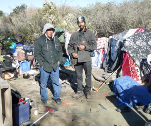 Alex Pena, left, and Joseph Lampkin stand at Pena's camp on the north end of the river encampment.