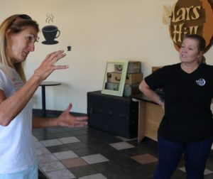 Beekeeper Valerie Filice, left, explains to Darla Hernandez, Mars Hill manager that the bees are not a problem.