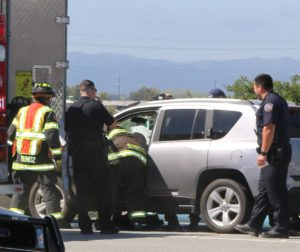 Hollister police and fire crews help injured driver.