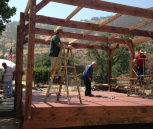 Don Pidd, on ladder, Delbert Doty, center, and volunteers help build new stage at SBC Historical Park