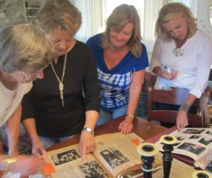 Lenore (from far left) and Madeline share the scrapbook with Vicki Fortino and Stephanie Hicks.