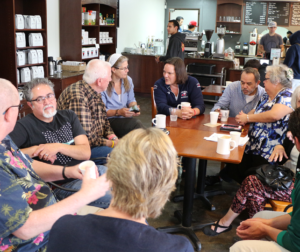 Dr. Kathleen Rose, (center in navy blue) talks with trustees, faculty and community members during the coffee held in San Juan Bautista.