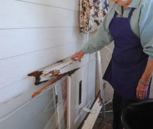 Naomi Medina inspects damage to the front door of her daughter's shop, Margot's, in San Juan Bautista