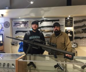 merican Armory Sales Manager Justin Olson and Owner Jesse Rodriguez pose in front of a gun