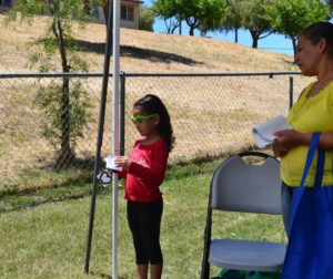 Yesenia Benavides receives an eye exam while her mom looks on.