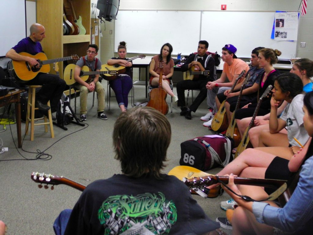 Youths studying guitar in a classroom setting.