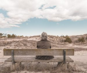 A person sits alone on the bench observing the scenery.