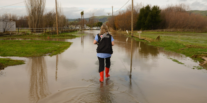 Photo of Red Cross volunteer walking through the flooded areas of Hollister during the Winter 2017 floods there.