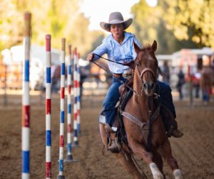 Lilla Bell weaves through a series of poles on her horse in the 14-18 year old pole bending division at San Benito County Fair's Junior Rodeo in 2017. Bell will compete at the Gilroy Rodeo this weekend. Photo by Joshua Miller.