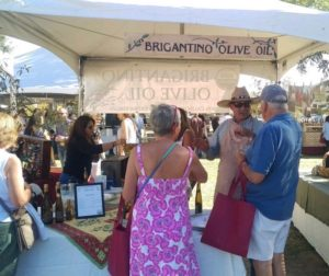 Dave Brigantino, co-owner of Brigantino Olive Oil, talks to people attending the Olive Festival about his product