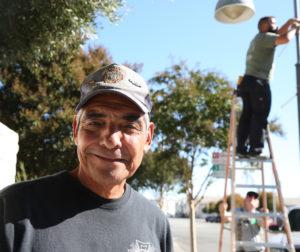 Bernie Ramirez smiles for the camera as crews put up banners around town