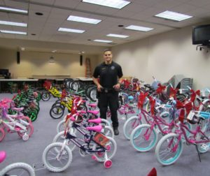 School Resource Officer Carlos Rodriguez stands by the 70 bikes given away for 2016 Wheels for Kids campaign.  BenitoLink file photo