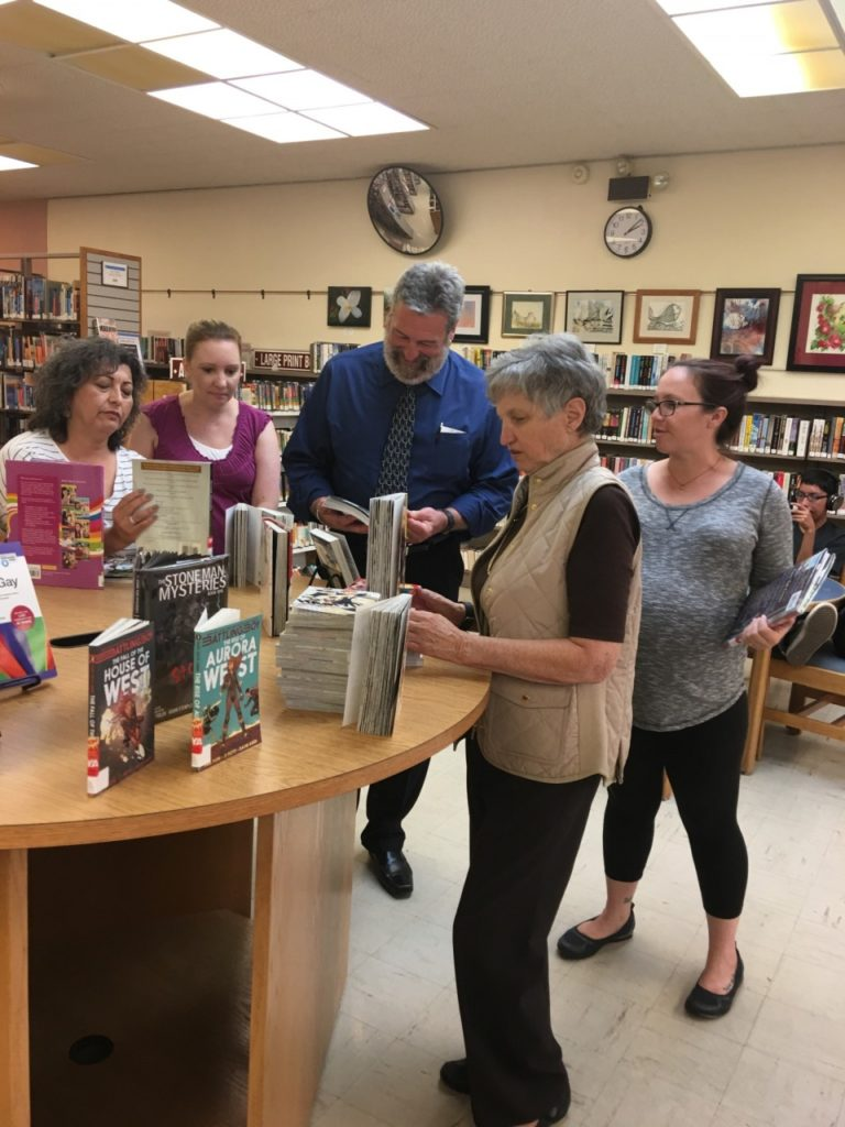Greg Lucas(center in blue), the state librarian takes a look at a display in the Hollister Library.
