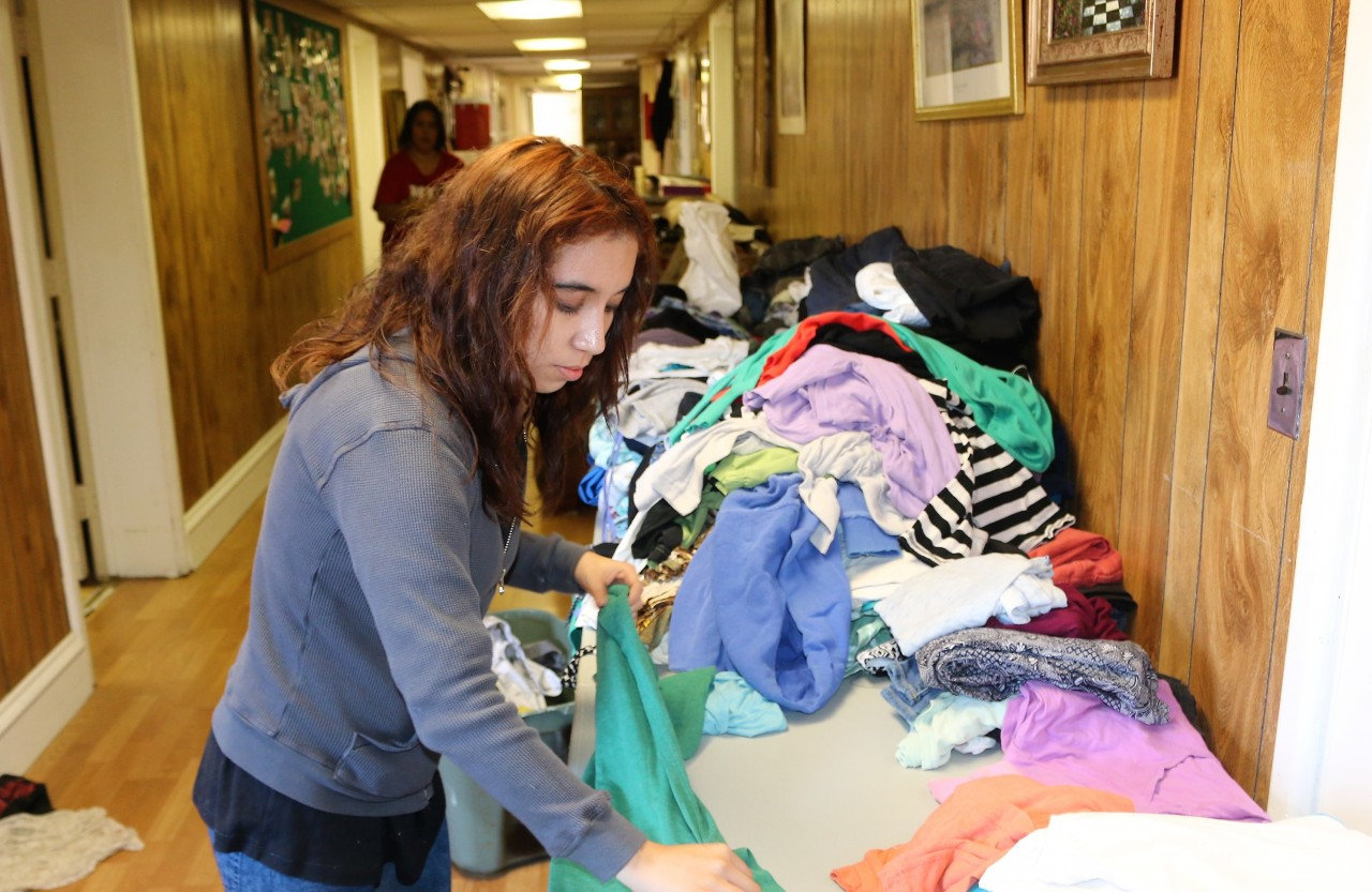 Volunteers help stock shelves and fold clothing.