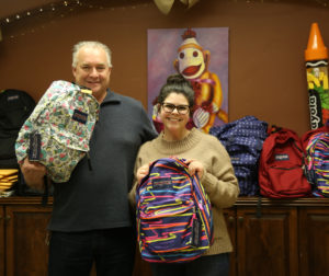 Cupertino Electric Senior Vice-president Bruce Baxter (left) and Lori Arnold with CASA surrounded by backpacks.