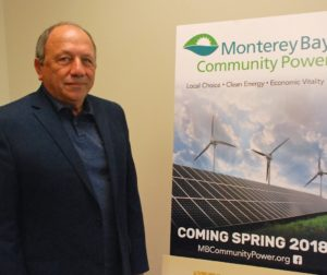 Tom Habashi, CEO of Monterey Bay Community Power, stands next to a poster about the agency in Watsonville.