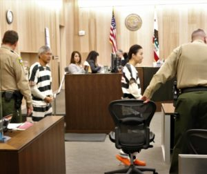 Sang Ji and Jung Choi are led into the courtroom in chains. Photos by John Chadwell.