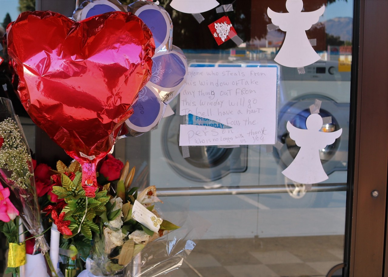 Memorial and angry note left on the door of Hollister Laundromat.