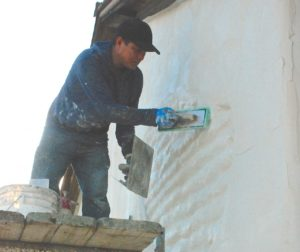 A worker with Gomes Plasticorners Inc. applies a finishing coat of plaster to the wall of the Juan de Anza House, fronting Franklin Street in San Juan Bautista on Feb. 3.