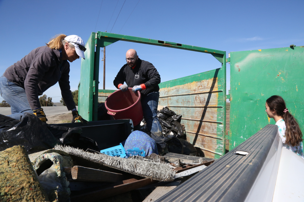 Stacie McGrady, Nathanael Lierly and Jennifer Hersh unload trash from the river into a dumpster provided by RJR Recycling.