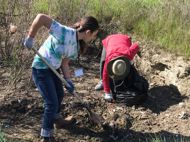 Jennifer Hirsch shovels trash with another volunteer along the banks of the San Benito River.  Photo by Leslie David