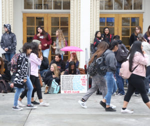 Students at the walkout last week protest campus violence as others head to class. Photo by Leslie David