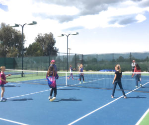 A group of Girl Scouts get tennis lessons from Ridgemark Tennis Club members.