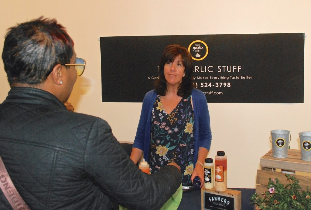 Michelle Doty talks about her company, That Garlic Stuff, to a woman attending the ninth annual Startup Challenge Monterey Bay in Salinas Saturday. Doty won the Main Street division and a prize of $10,000. Photo by Tom Leyde.