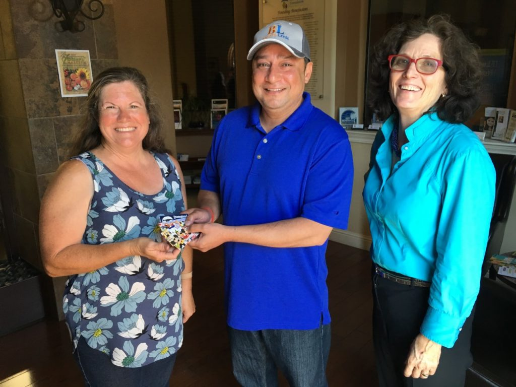 BenitoLink Board President Rohit Sharma (center) hands BenitoLink donor (left) Debbie Simmons four Disneyland tickets. BenitoLink Executive Director Leslie David is on the far right.