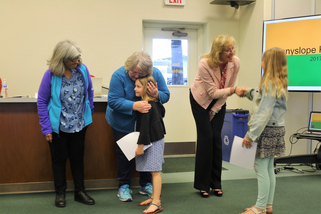 Dr. Lisa Andrew, far right, greets a young student during an awards presentation.