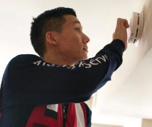 A Red Cross worker installs a smoke alarm. Photo provided.