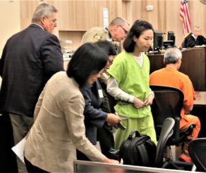 South Korean citizen and suspect Jung Choi enters courtroom as her accused accomplice Sang Ji sits nearby. Photos by John Chadwell.