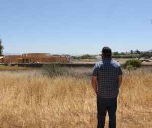 Matthew Manning watches the construction of houses in the Rancho Vista development. Photo by Noe Magaña.