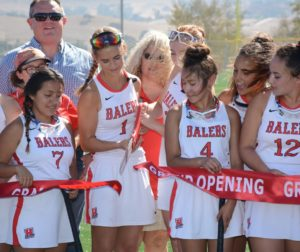 Members of the Girls' Field Hockey team cut the grand opening ribbon as school board members and the crowd looked on. Photo by Ed Wong.