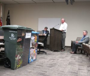 Two sample carts displayed during the meeting as Recology General Manager Phil Couchee speaks to the Hollister City Council. Consultant Kevin McCarthy sits to his left. Photo by Noe Magaña.
