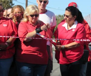 Terri Wilson (left) and Mercedes Berglund cut the ribbon with school staff behind them. Photo by Noe Magaña.