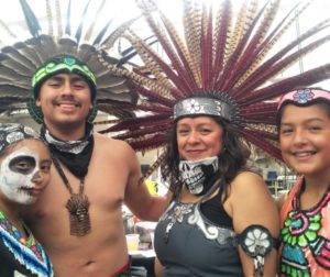 Camaxtli Torres (second from left) performed with his family and an Aztec dance group at Saturday's event. Photo by Becky Bonner.