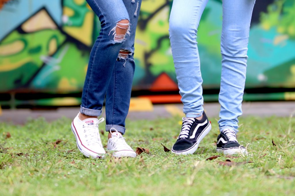 Two teens wearing jeans and sneakers. Photo courtesy of Pexels.