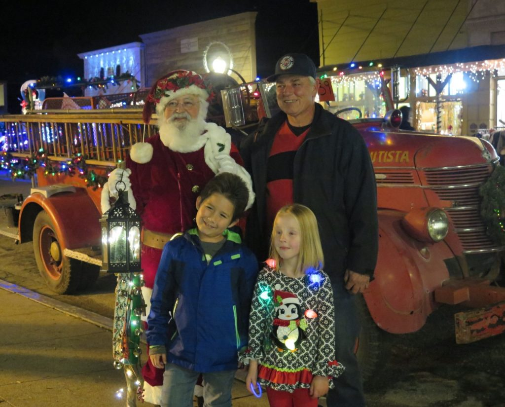 Santa (resident Max Martinez) poses with parade attendees. Photo by Becky Bonner.