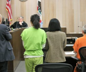 Judge Steven Sanders looks over his calendar to determine when murder suspects Jung Choi (left) and Sang Ji (right) will return to court. Photo by John Chadwell.